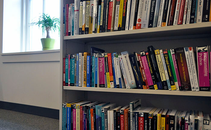 Bookshelf in the Caktus office with 3 shelves full of various books on web development and other technical topics