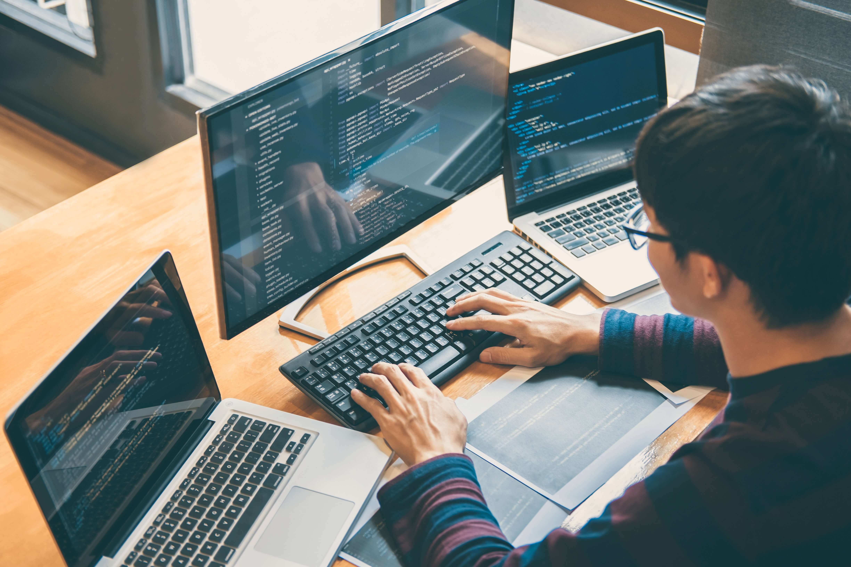 Developer monitoring three screens