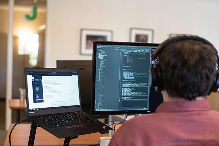Developer looking at computer monitors