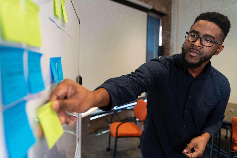 QA expert putting note on whiteboard